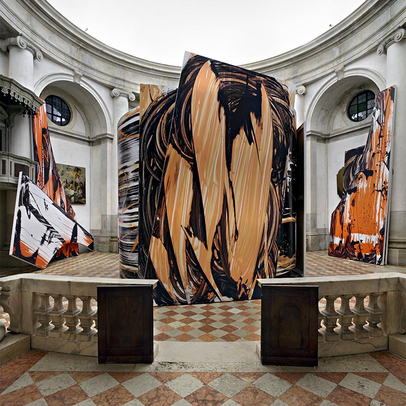 Circular room with three large vinyl sculptures printed with enlarged brush strokes of black, white and orange paint.