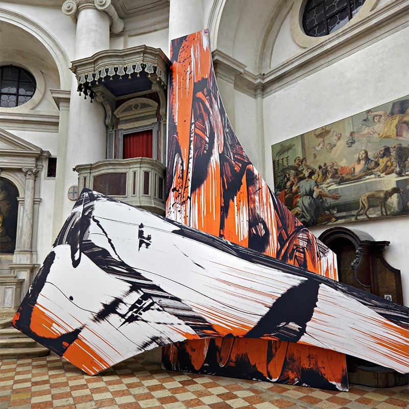 Two large fragmented vinyl sculptures printed with enlarged brush strokes of black, white and orange paint resting around a raised pulpit and in front of a classical religious painting.