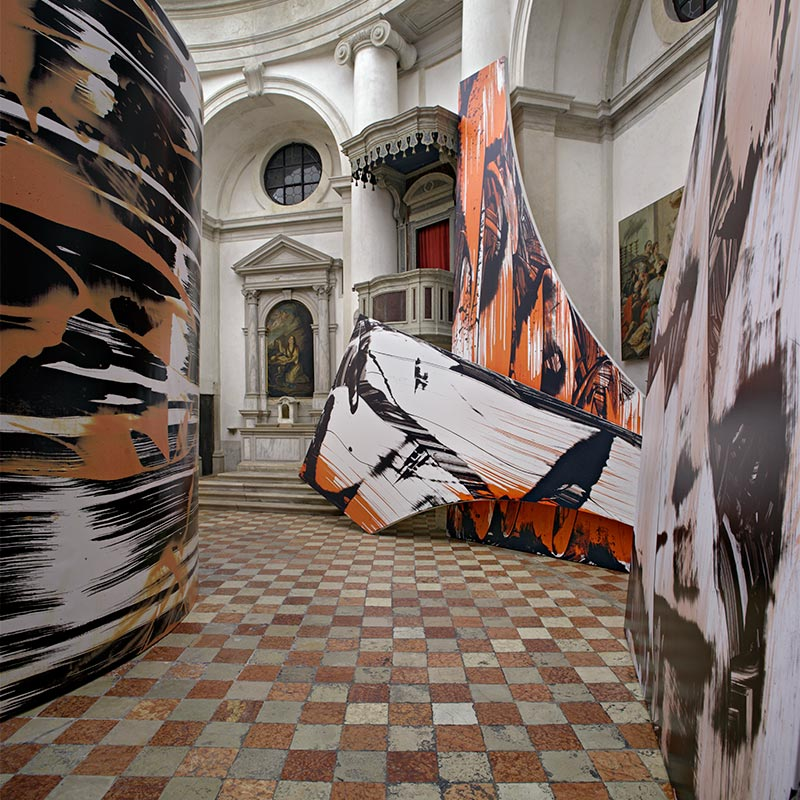 Three large vinyl sculptures printed with enlarged brush strokes of black, white and orange paint. One sculpture forms a large cylinder in the center of the room and the other two rest around a raised pulpit. Checkered terracotta tiles cover the floor.