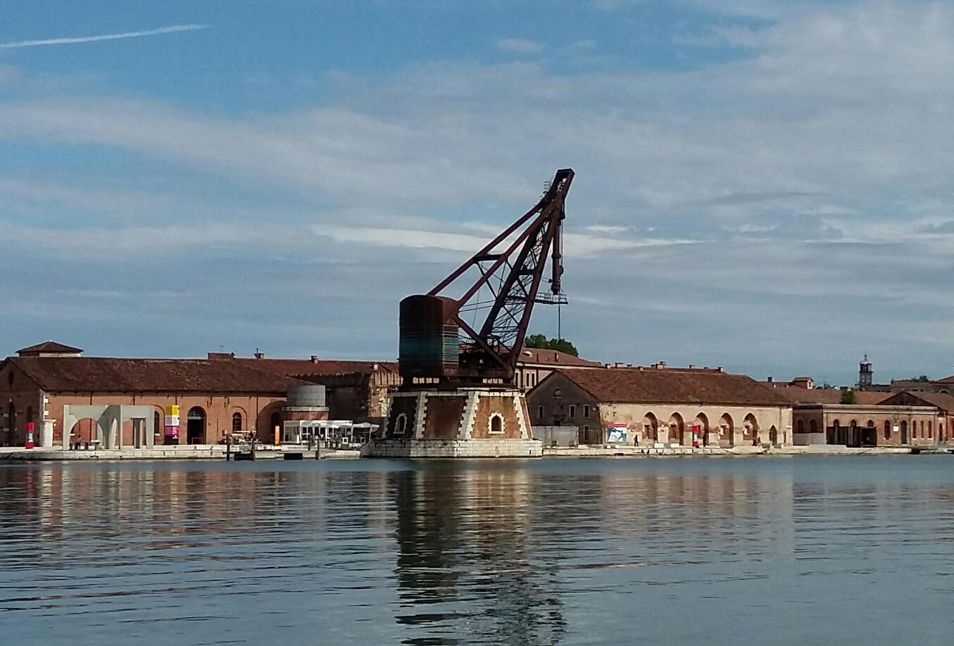 Long shot of the Arsenale, looking across the water to Tesa dell'Isolotto, showing the 19th century hydraulic crane located outside the New Zealand Pavilion.