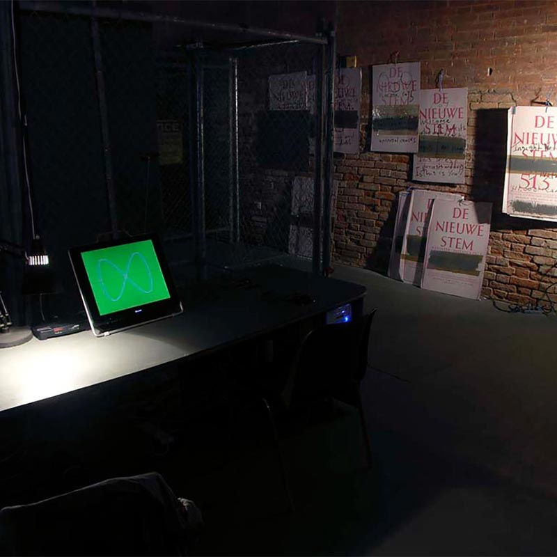 Long grey work bench, illuminated by single desk lamp with a computer monitor displaying white loop of infinity on green background. Adjacent red brick wall has an arrangement of six white posters with 1946 left-wing Dutch journal text printed in red.