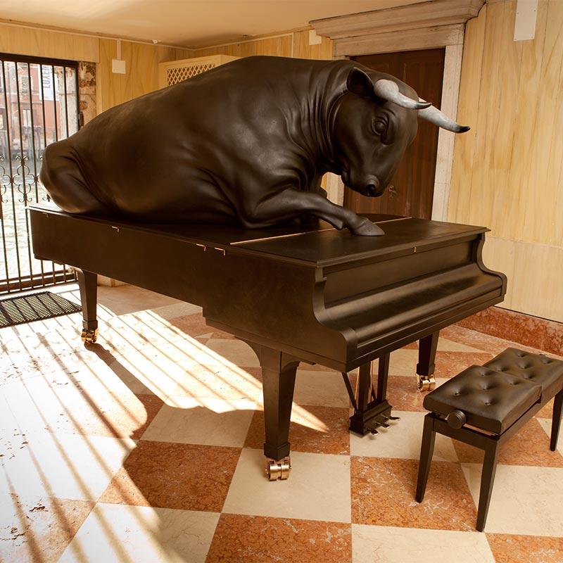 Life-size, black Spanish fighting bull in bronze, weighing 932 kilograms lying on top of bronze concert grand piano inside Palazzo Loredan dell'Ambasciatore.