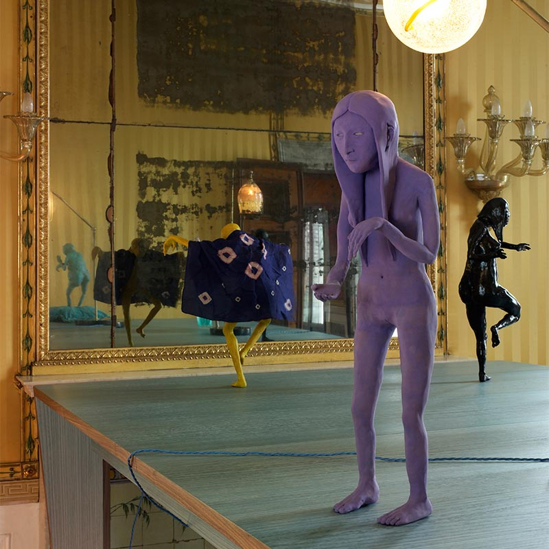 Three small hand-crafted sculptures of human figures in different states of motion presented atop a wooden table in front of an antique mirror. Foreground of image stands a lean, purple-coloured, naked female sculpture with long hair.