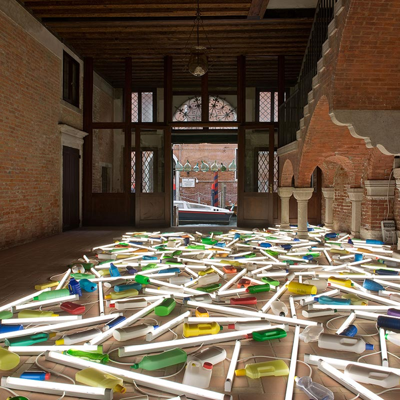 Florescent tube lights interwoven with mixture of colored plastic bottles covering the floor of La Pietà.