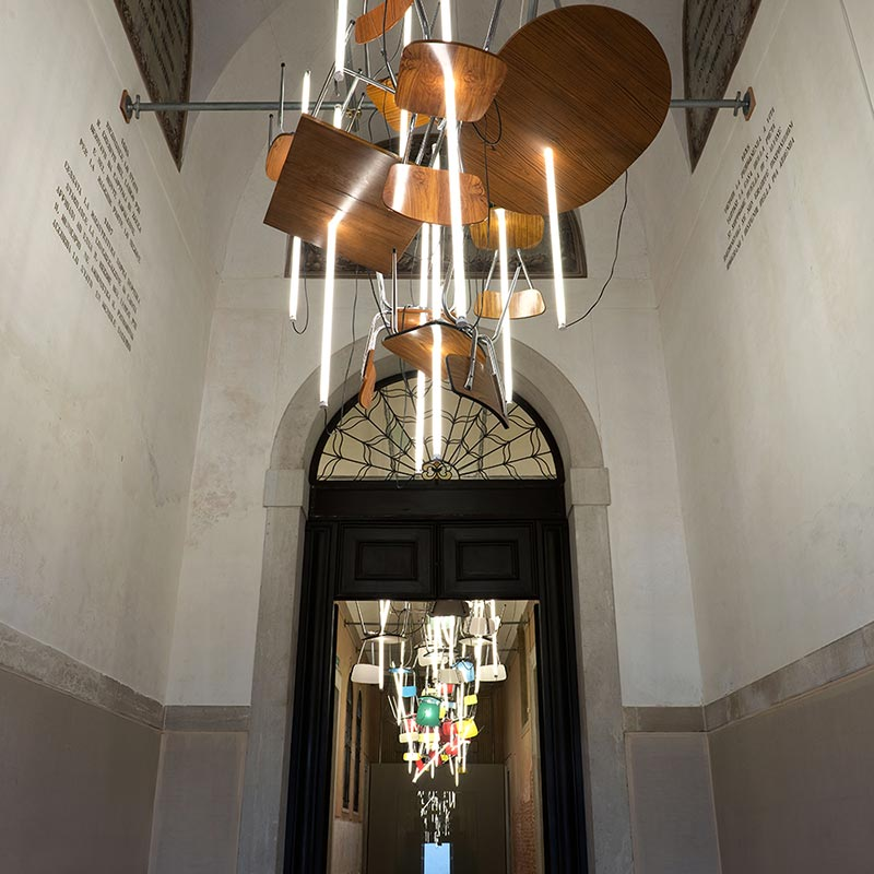 Sculpture suspended from high corridor ceiling, made of seven Formica chairs and two tables illuminated by fluorescent light tubes lanced through the upside-down dinner setting.