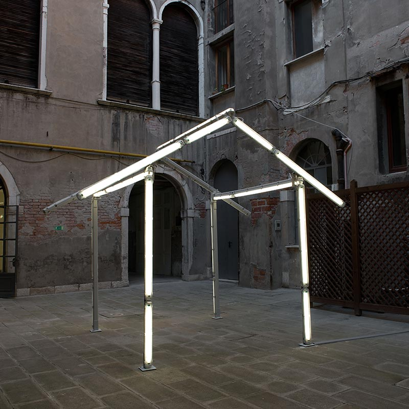 Sculpture forming the roof and wall frame of a house constructed from twenty-two fluorescent light tubes presented in grey internal courtyard of La Pietà.