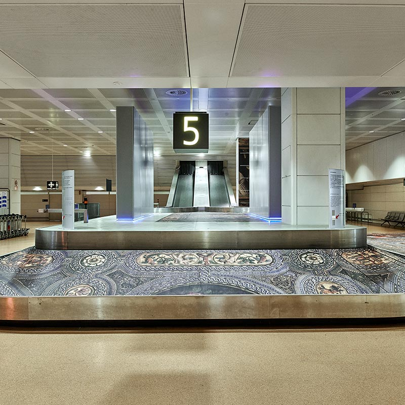 Baggage belt at Marco Polo Airport, covered in laminated print of a section of the painted Renaissance ceiling of the Biblioteca Nazionale Marciana Library.