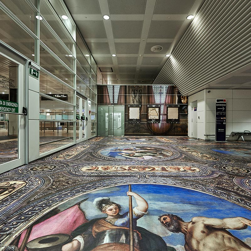 Floor at Marco Polo Airport entrance covered in laminated print of a section of the painted Renaissance ceiling of the Biblioteca Nazionale Marciana Library.