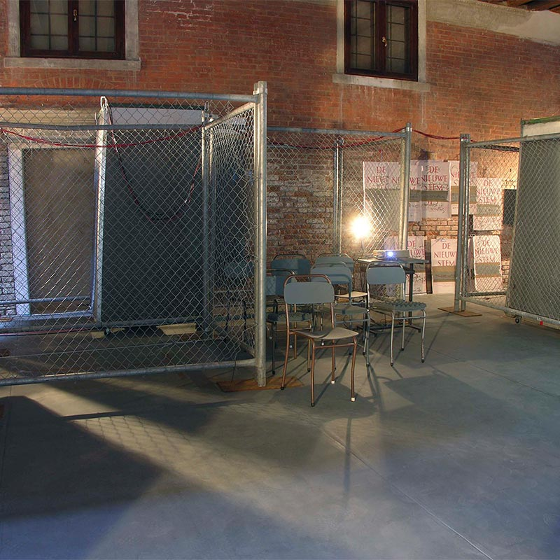 Wire fencing creating industrial zone within brick room. Back lighting casting multiple shadows across the floor with seven grey chairs positioned in three rows on right hand side.