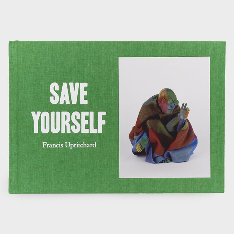 Green fabric book cover with image of crouched multi-coloured, male sculpture, wearing glasses and thick-weave wrap, right hand held up in a gesture of benefaction.