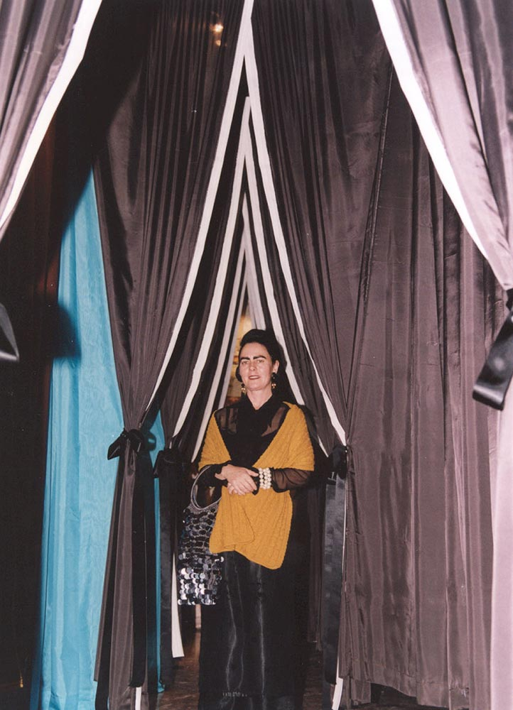 Jacqueline Fraser standing between two rows of draped curtains.
