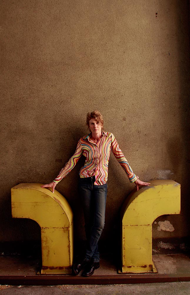Judy Millar standing between two curved yellow metal air vents.