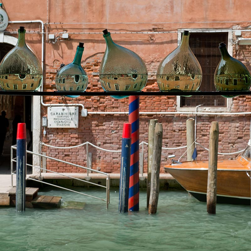 Six tear-shaped glass bottles in various sizes and containing water which creates a reflection of the red brick building on the opposite side of the canal, presented in a row across a steel shelf spanning the external doorway in front of the canal