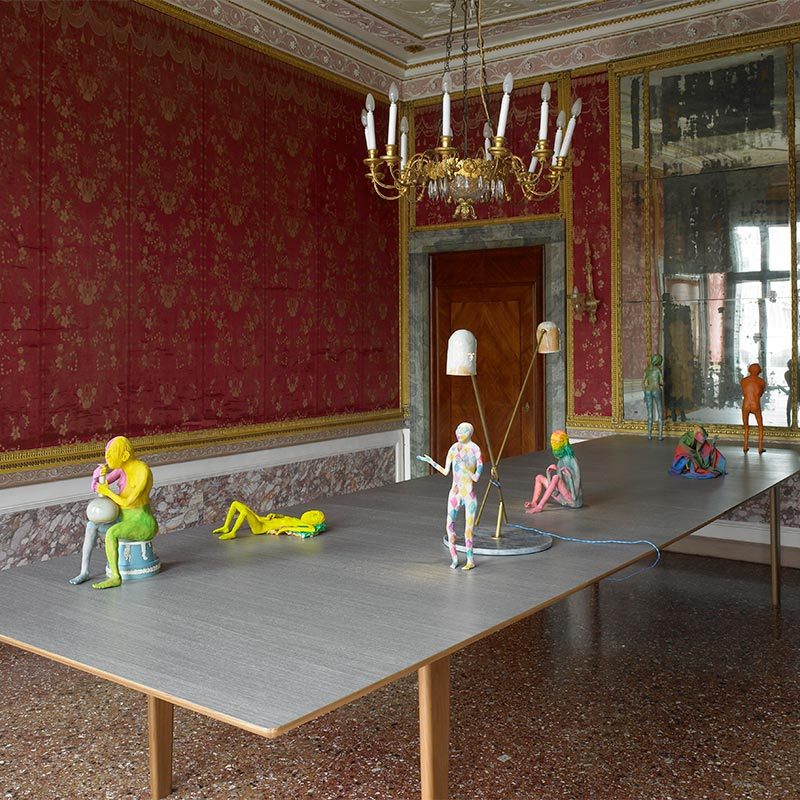 Seven small hand-crafted sculptures of human figures in different states of motion and gesture presented atop a wooden table in front of an antique mirror.