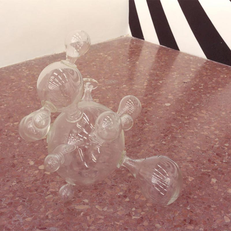 Clear glass sculpture positioned on the floor consisting of different sized bulbs coming from a central circular form, representing science's best guess about the structure of the universe and its expanding and contracting behaviour.