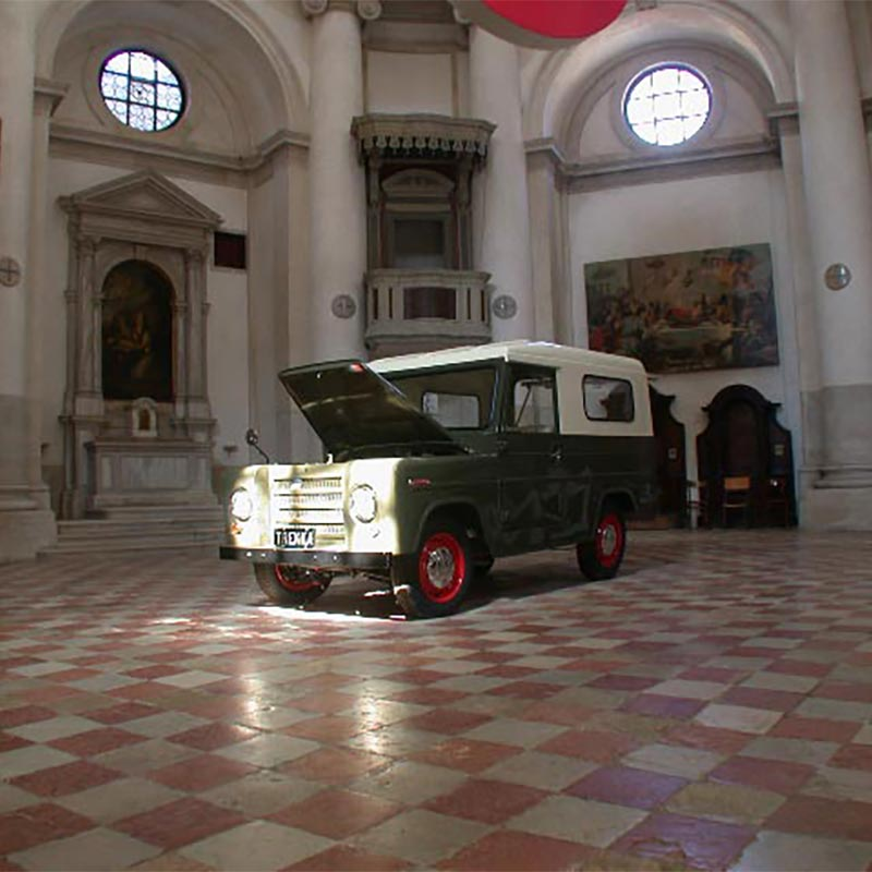 Trekka motor vehicle with bonnet up positioned in the middle of La Maddelena church with original classical religious paintings in the background.