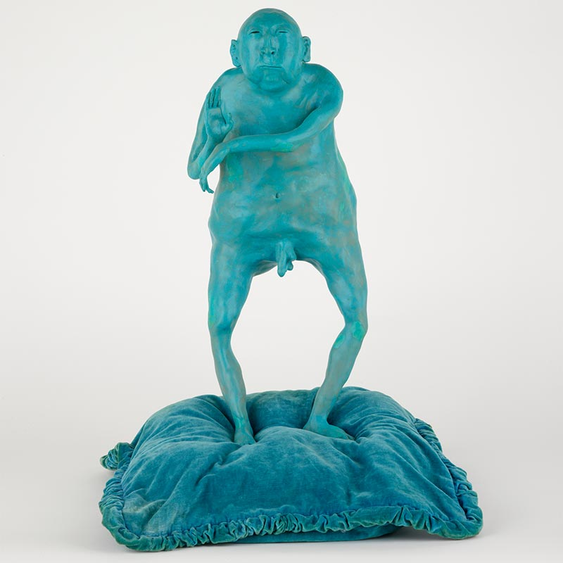Teal-coloured sculpture of an overweight, elderly, bi-gonaded male standing on top of a velvet cushion and imitating a tai chi-like movement.