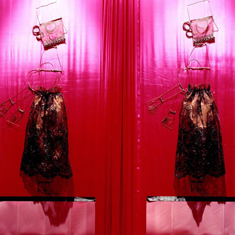 Mixed media sculpture of two female figures made of wire and textile on hot pink curtained background.