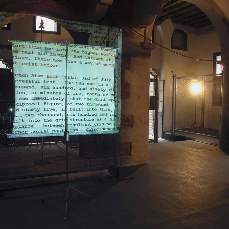 Projector screen in front of wire fence displaying text discussing atomic bomb testing.