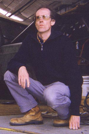 Michael Stevenson crouching in front of a Trekka motor vehicle.