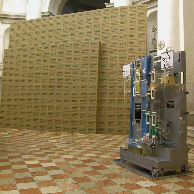 Moniac computer in front of two high walls of stacked New Zealand creamery butter packing boxes. A Perspex labyrinth, the Moniac was a water-driven analogue computer; a hydraulic model of a national economy.