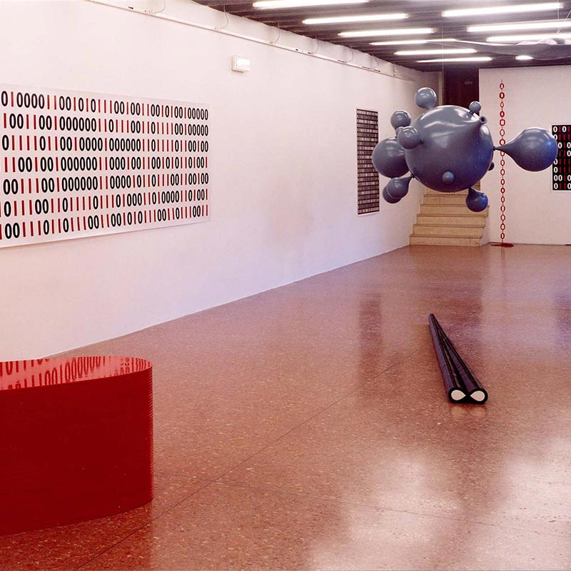Central hanging blue fibreglass sculpture surrounded by long rectangular sheets of printed binary code on each wall.