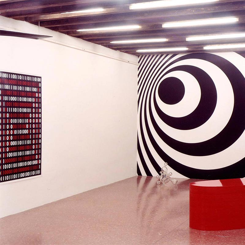 Screen-printed black and white spiral pattern covering back wall with a stack of red lacquered sheets forming a sculpture positioned on the floor in front.
