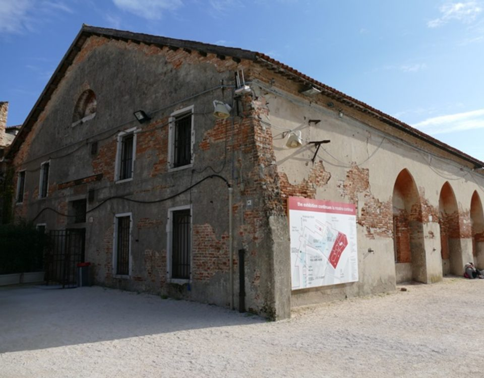 Outside view of Tesa dell'Isolotto. An old, long brick building, with craved archways cut into the right side of the building.